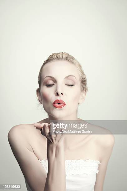 Young woman blowing kiss with eyes closed, portrait