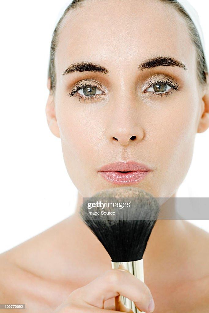 Young woman blowing makeup brush : Stock Photo