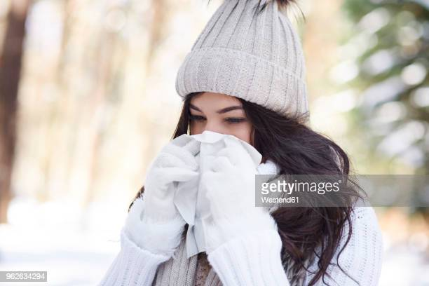 young woman blowing nose in winter - handkerchief stock photos and pictures