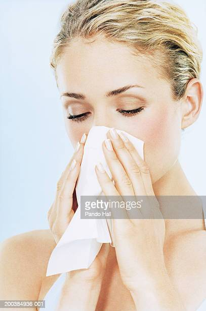 Young woman blowing nose on tissue, close up