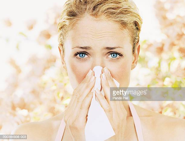 young woman blowing nose on tissue, close up, portrait - blowing nose stock pictures, royalty-free photos & images