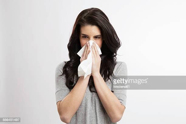 young woman blowing nose - sonarse fotografías e imágenes de stock