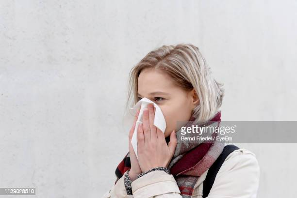 young woman blowing nose while standing against wall - infectious disease stock pictures, royalty-free photos & images