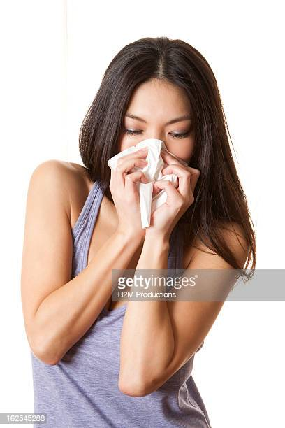 Young Woman Blowing Nose With Tissue