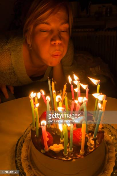 Young woman blowing out birthday candles