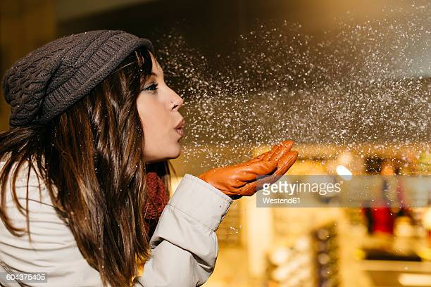 young woman blowing snow in the air at night - 吹く ストックフォトと画像