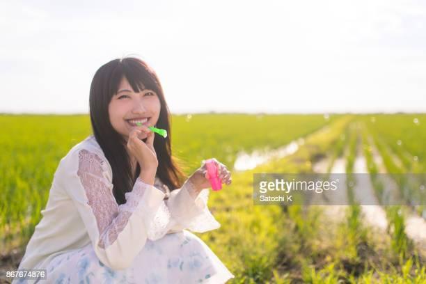 jeune femme soufflant des bulles de savon dans la rizière - femme japonaise belle photos et images de collection