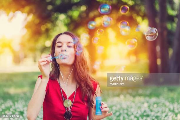 Jeune femme soufflant des bulles de savon dans le parc