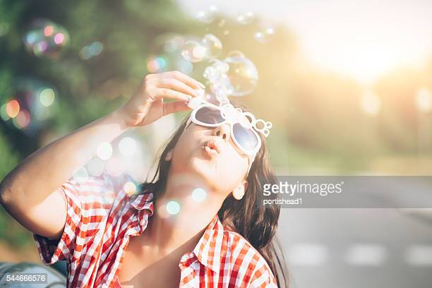 Young woman blowing soap bubbles outdoor