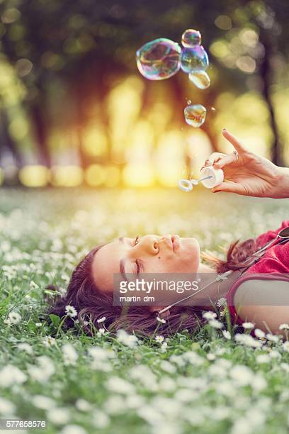 Junge Frau blowing soap bubbles