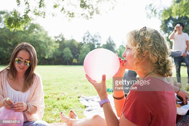 Young woman blowing up balloon at park party