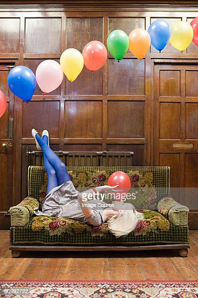 A young woman blowing up balloons