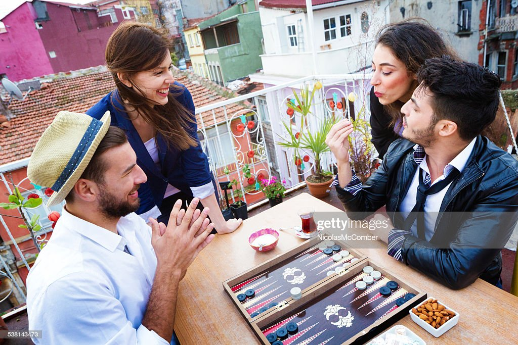 Young woman blows on dice for luck during backgammon game : Stock Photo