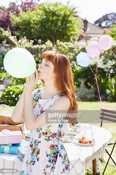 young woman blows up balloon.