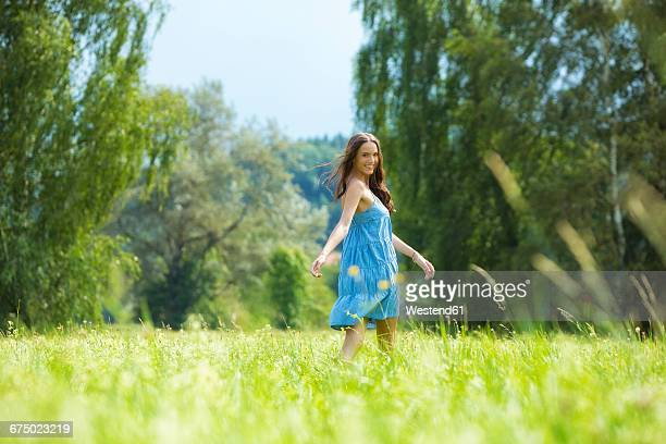 Young woman, blue dress, on meadow