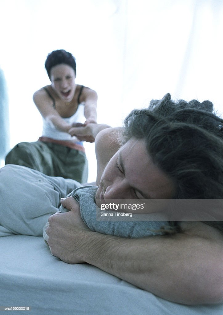 Young woman, blurred, in background, pulling young man, in foreground, out of bed : Stockfoto