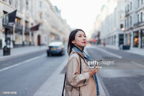 young woman booking taxi on mobile app on the city street - waiting stock pictures, royalty-free photos & images