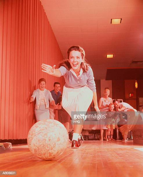 young woman bowling, family watching in background - bowling stock pictures, royalty-free photos & images