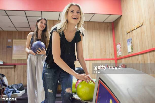 A young woman bowling.