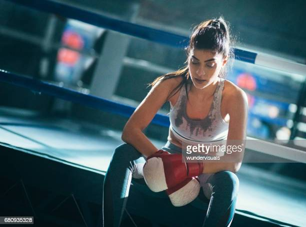 Young woman boxer tired after fighting in the boxing ring