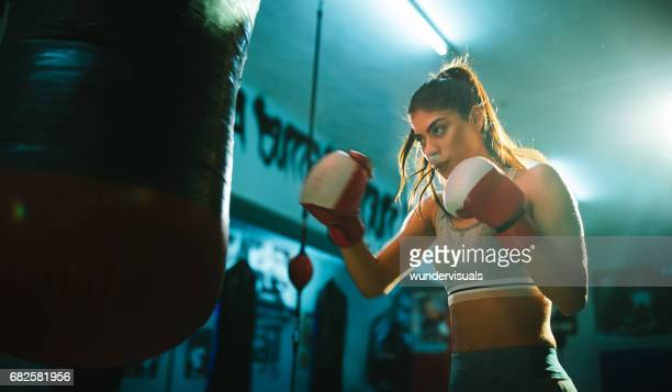 Young woman boxer training with a punching bag