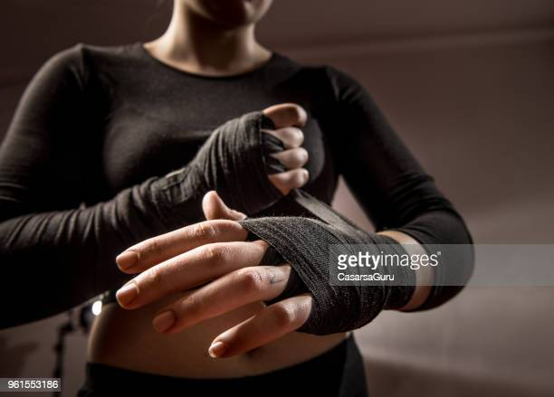 young woman boxer tying protective bandage around her wrists - women's boxing stock pictures, royalty-free photos & images