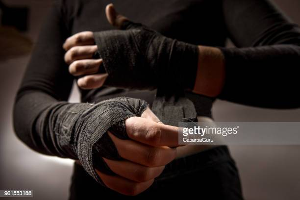 young woman boxer tying protective bandage around her wrists - combat sport stock pictures, royalty-free photos & images