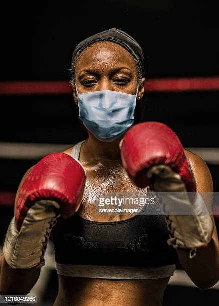 young woman boxer wearing healthcare face mask. - knockout stock pictures, royalty-free photos & images