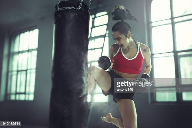 young woman boxing workout in an old dark gym - taking a shot sport stock pictures, royalty-free photos & images