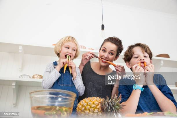 young woman, boy and girl in kitchen, fooling around, using carrots as false teeth - nanny stock pictures, royalty-free photos & images