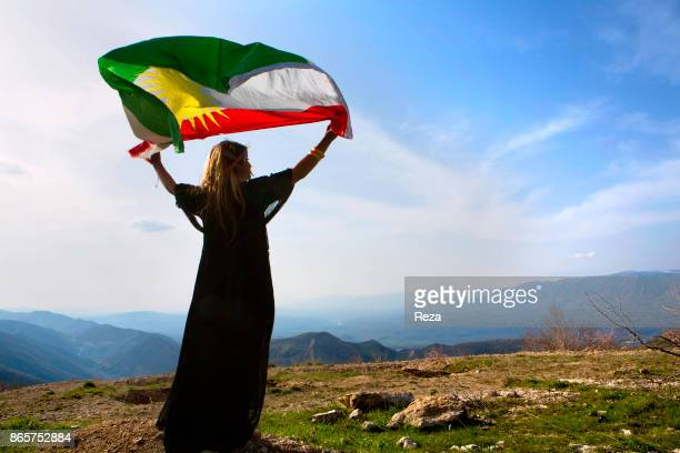 A young woman brandishes the Kurdish flag as she dances with family and friends during a picnic to celebrate Nowruz on the first days of spring