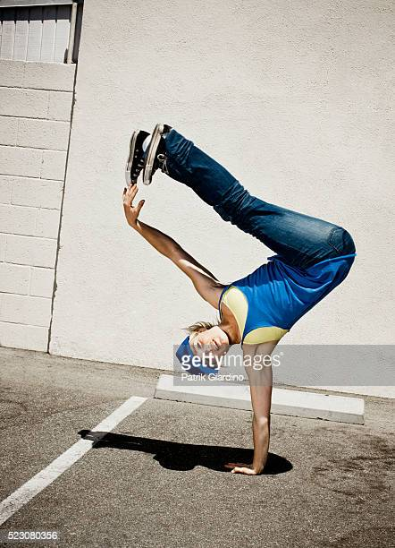 Young woman breakdancing in parking lot