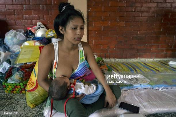 A young woman breastfeeds her child at a shelter in Mocoa Putumayo department southern Colombia on April 3 2017 Residents of Mocoa were Monday...