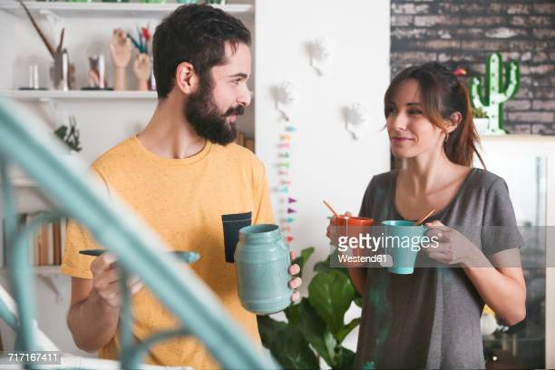 Young woman bringing two cups of tea while her boyfriend painting an armchair