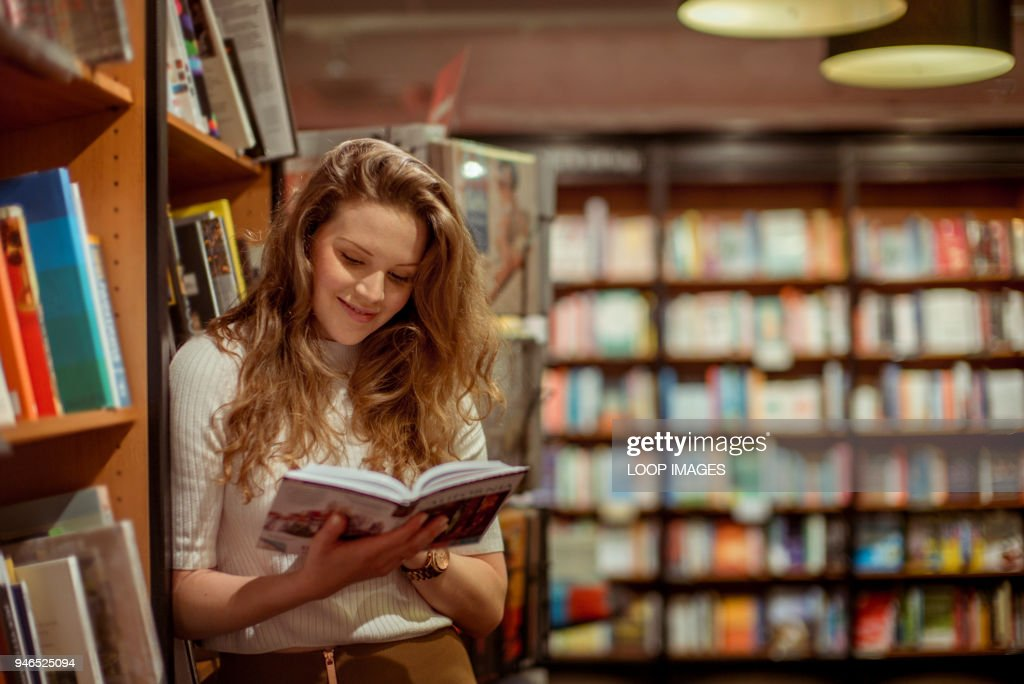 A young woman browses in a book store : Stock Photo