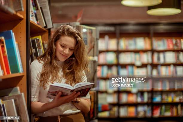 a young woman browses in a book store - book shop stock pictures, royalty-free photos & images