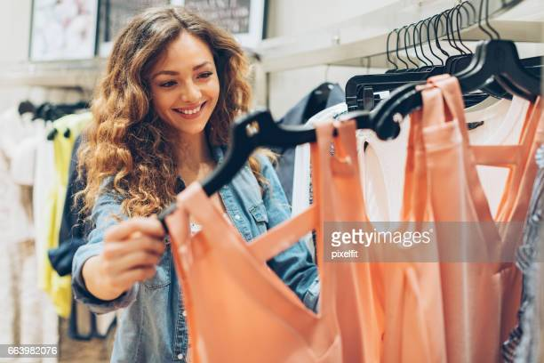 young woman browsing in the fashion store - dress stock pictures, royalty-free photos & images