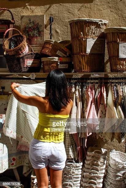 A young woman browsing linen products at a craft homewares shop in Nice France