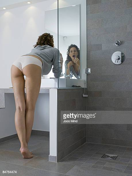 young woman brushes her teeth, rear view