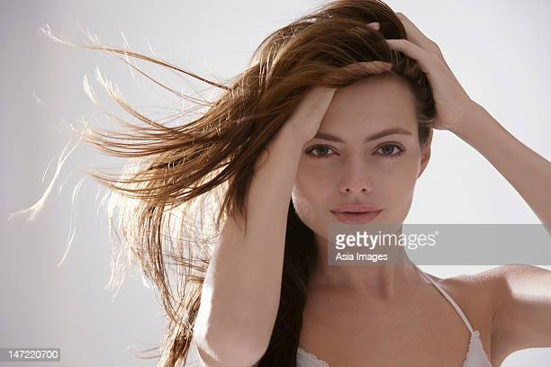 young woman brushing both hands through her hair - 髪に手をやる ストックフォトと画像