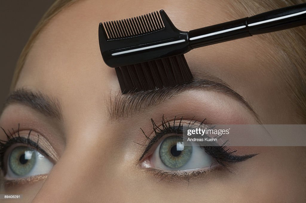 Young woman brushing eyebrows, close up. : Stock Photo