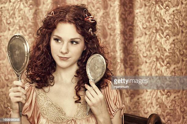 young woman brushing her hair - hand mirror stock photos and pictures