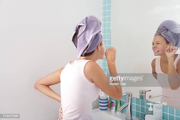 Una mujer joven cepillar los dientes