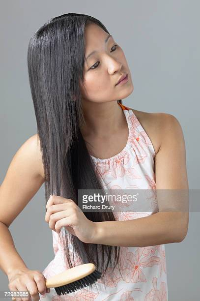 young woman brushing long hair - richard drury stock pictures, royalty-free photos & images