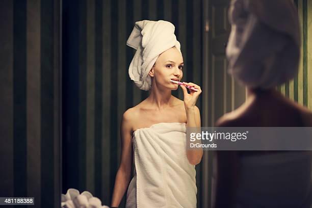 Young woman brushing teeth in bathroom mirror
