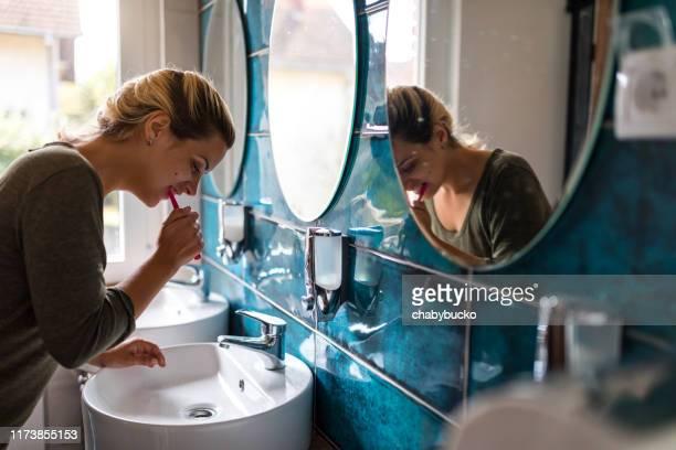 jeune femme brossant des dents - dents photos et images de collection