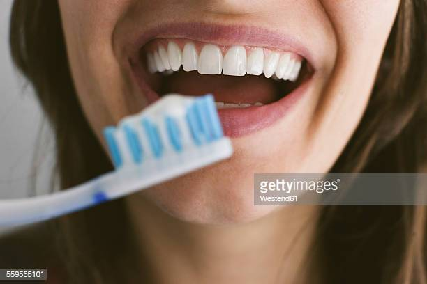 young woman brushing teeth - toothbrush stock pictures, royalty-free photos & images