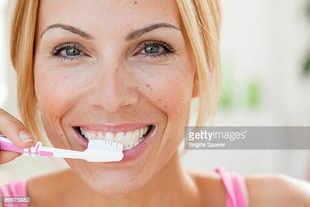 young woman brushing teeth