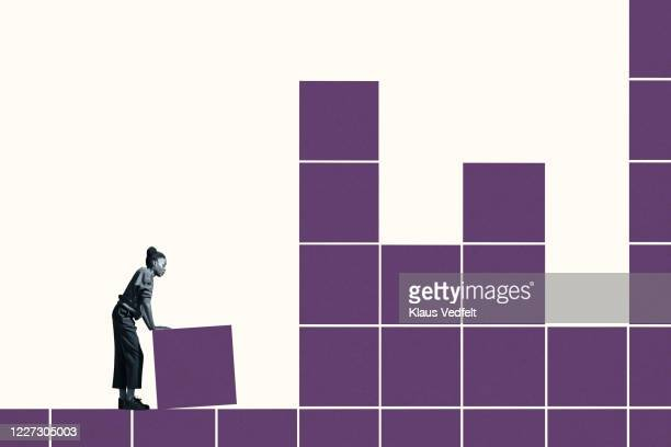 young woman building grid with purple blocks - putting stock pictures, royalty-free photos & images
