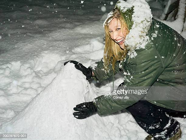 Young woman building snowman, laughing, portrait